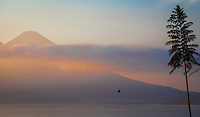 Sunrise reflects off a volcano and Lake Atitlan in Guatemala