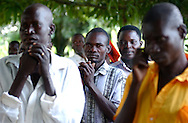 Samuel Ogwal, 30, prays with neighbors in their little village of Oculokori, in northern Uganda. Ogwal, as a young boy, was abducted by the LRA (Lord's Resistance army) and was  forced to teach children to kill and to watch them die, to deliver beatings and conduct ritualistic murders -- he was now facing a new kind of terror: returning home to the uncertain judgment of family and friends who had been brutalized by rebels like him.   (PHOTO MIGUEL JUAREZ LUGO).
