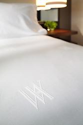 Marriott Hotel bedroom with white sheet set and queen bed Monogram