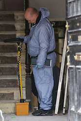 © Licensed to London News Pictures. 25/01/2020. London, UK. A forensic officer inside a property on Mount Pleasant Road in Clapton, East London. Police launch a murder investigation at a residential property following fatal stabbing after 11pm on Friday 24 January following reports of a disturbance. A man was found with stab injuries inside the property and died later. A 27 year old man was arrested at the scene on suspicion of murder. Photo credit: Dinendra Haria/LNP