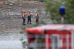 © Licensed to London News Pictures. 04/08/2019. Whaley Bridge, UK. RNLI and emergency crew are seen on dry areas of the bed of the reservoir as the water level is reported as being more than 30% lower than yesterday (Saturday 3rd August) . More rain is forecast today (Sunday 4th August) in the town of Whaley Bridge in Derbyshire after earlier heavy rain caused damage to the Toddbrook Reservoir , threatening homes and businesses with flooding. Photo credit: Joel Goodman/LNP