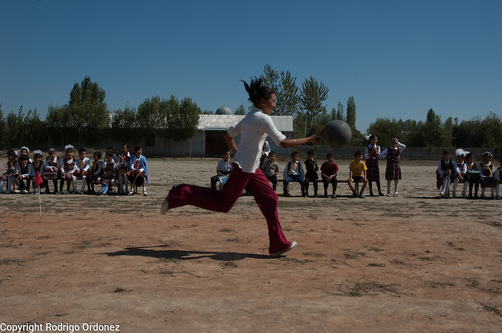A girl participates in a basketball relay race as other children watch, during the last day of activities at the child-friendly space located in Alim Tepe School (in Osh, Kyrgyzstan), established and supported by Save the Children. The closing celebrations included a sports competition, games and a cake.