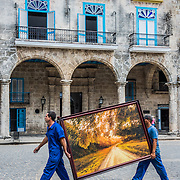 Two men transporting a painting in Havana, Cuba
