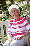 Elderly Woman Sitting On A Bench In A Rose Garden Courtyard