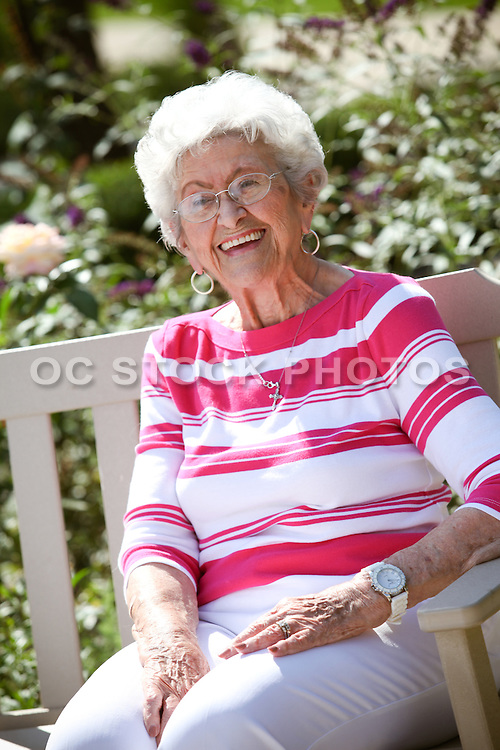 Elderly Woman Sitting On A Bench In A Rose Garden Courtyard