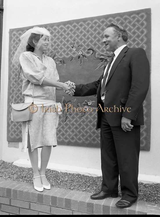 """Best Dressed Lady at Phoenix Park Races.1984..11.08.1984..08.11.1984.11th August 1984..A competition,sponsored by V'Soske Joyce,was held at the Phoenix Park Racecourse,Dublin.The prize of a hand tufted rug was awarded to the """"Best Dressed Lady"""" on Ladies Day at the racecourse. The eventual winner was Brianne Leary from Los Angeles,California..Image of Ms Brianne Leary taken with the Sponsors Director, Mr Michael Dixon as they pose in front of her prize, a hand tufted Rug."""