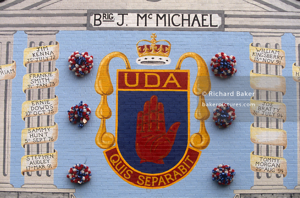 A loyalist wall mural in a protestant area of Belfast showing the Red Hand Defender emblem and Latin slogan using the Latin motto 'Quis Separabit' meaning 'Who shall separate us?' - a detail of a political painting in a street off the Shankill Road in Belfast, Northern Ireland.