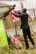 An activist adds signs to a makeshift memorial wall on the spot where unarmed motorist Walter Scott was gunned down by police April 12, 2015 in North Charleston, South Carolina. About 100 people showed up for the brief vigil following a healing service at Charity Mission Baptist Church.