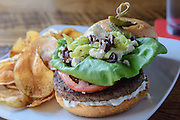 The GreekBurger on a brioche bun with feta cheese, lettuce, tomato, black olives and pepperoncini with Tzatziki sauce and served with house-made chips at Somewhere restaurant at 1135 Bardstown Road, next to Nowhere bar. July 26, 2016