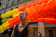 Volunteer Kent Chua standing in front of the Pride balloon arch. Chua will be among those carrying the arch down the parade route.