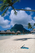 Bora Bora Lagoon Resort, Tahiti: snorkeling gear on beach, bungalows on lagoon; with Mount Pahia in the distance.