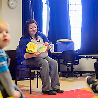 Library clerk Lynette Curley reads aloud to a group of young children during Toddler Time at the Gallup Children's Library Wednesday.