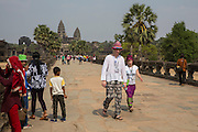 White European tourists dressed in colourful clothes walk along the stone walkway surrounding Ankor Wat temple complex in Krong Siem Reap, Cambodia. Angkor Wat is a temple complex in Cambodia and the largest religious monument in the world, with the site measuring 162.6 hectares. It is Cambodia's main tourist destination.