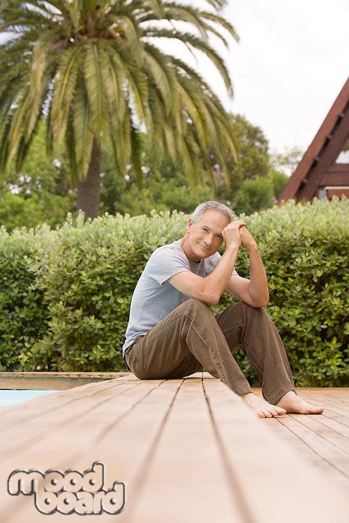 Middle-aged man sitting by pool portrait