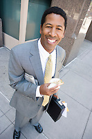 Portrait of businessman with newspaper and sandwich, smiling