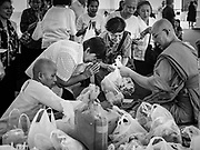 "11 APRIL 2017 - BANGKOK, THAILAND: A Buddhist monk accepts merit making offerings from people at Wat Chana Songkhram in Bangkok during a Songkran merit making service. Songkran is the traditional Thai Lunar New Year. It is celebrated, under different names, in Thailand, Myanmar, Laos, Cambodia and some parts of Vietnam and China. In most places the holiday is marked by water throwing and water fights and it is sometimes called the ""water festival."" This year's Songkran celebration in Thailand will be more subdued than usual because Thais are still mourning the October 2016 death of their revered Late King, Bhumibol Adulyadej. Songkran is officially a three day holiday, April 13-15, but is frequently celebrated for a full week. Thais start traveling back to their home provinces over the weekend; busses and trains going out of town have been packed.     PHOTO BY JACK KURTZ"