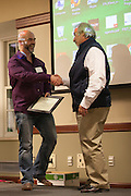 Dr. Ronan Carroll shakes hands with Dr. John Kopchick onstage after recieving his John J. Kopchick Molecular and Cellular Biology Translational Biomedical Sciences Faculty Support Fund award in Nelson Commons on Saturday, November 14, 2015. Photo by Kaitlin Owens