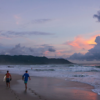 Surfers at sunset on Playa Carmen near Banana Beach lounge in Santa Teresa, Costa Rica.