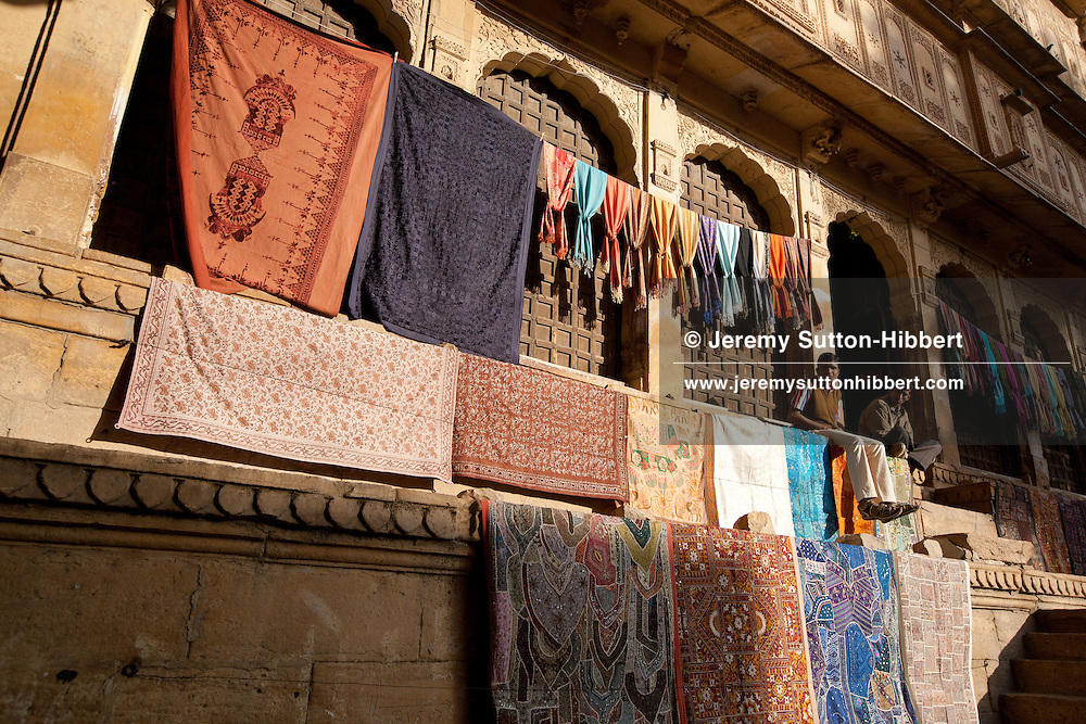 Textiles for sale on wall of Fort Palace, in Dashera Chowk, in Jaisalmer Fort, in Rajasthan, India, on 23rd December 2011.