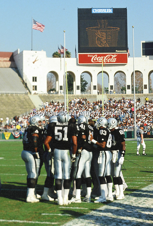 A group of Los Angeles Raiders players huddle near the sideline in this general view photo of the stadium and Peristyle end of the Los Angeles Coliseum during the NFL AFC Wild Card postseason playoff football game against the Denver Broncos on Jan. 9, 1994 in Los Angeles. The Raiders won the game 42-24. (©Paul Anthony Spinelli)