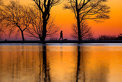 © Licensed to London News Pictures. 29/12/2016. Bradford UK. A dog walker strolls around the lake at Harold Park in Bradford at Dawn this morning on another freezing but sunny morning.Photo credit: Andrew McCaren/LNP