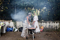 "ROME, ITALY - 3 JULY 2016: (L-R) Gipsy Queens members Aninfa Hokic (31) and Codruta Balteau (24) grill meat at their food stand at the iFest, an alternative music festival  in Rome, Italy, on July 3rd 2016.<br /> <br /> The Gipsy Queens are a travelling catering business founded by Roma women in Rome.<br /> <br /> In 2015 Arci Solidarietà, an independent association for the promotion of social development, launched the ""Tavolo delle donne rom"" (Round table of Roma women) to both incentivise the process of integration of Roma in the city of Rome and to strengthen the Roma women's self-esteem in the context of a culture tied to patriarchal models. The ""Gipsy Queens"" project was founded by ten Roma women in July 2015 after an event organised together with Arci Solidarietà in the Candoni Roma camp in the Magliana, a neighbourhood in the South-West periphery of Rome, during which people were invited to dance and eat Roma cuisine. The goal of the Gipsy Queen travelling catering business is to support equal opportunities and female entrepreneurship among Roma women, who are often relegated to the roles of wives and mothers."
