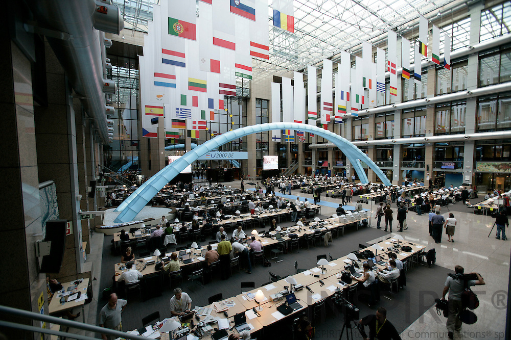 BRUSSELS - BELGIUM - 21 JUNE 2007 -- EU-SUMMIT -- Journalist working in the big press room in the council during the summit with the EU member states flag hanging over them.  Photo: Erik Luntang