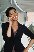 Business woman using mobile phone standing outside office building