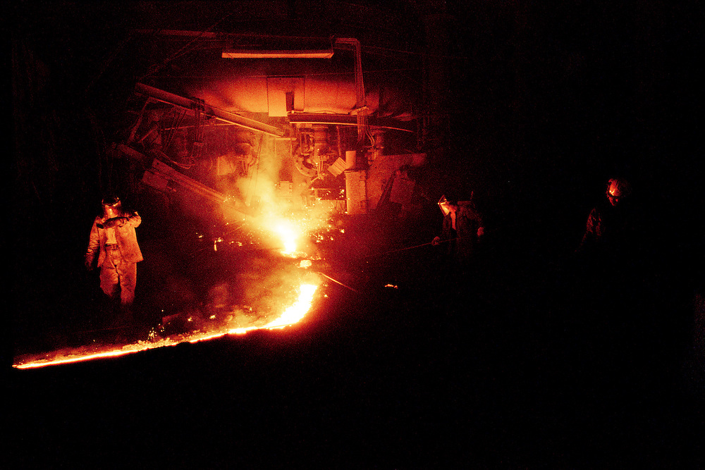Workers at an iron and steel plant. These workers earn 1000RMB (US$100) per month with only 1 full day off every month. They are adding a flux, whilst air is being blown into the furnance to combust with the carbon and silicon in the molten iron. The process of making steel is highly polluting. China is now the number one producer of steel, CO2 and Sulphur Dioxide, a major constituent in acid rain. Tonghua, Jilin Province, China. 2006