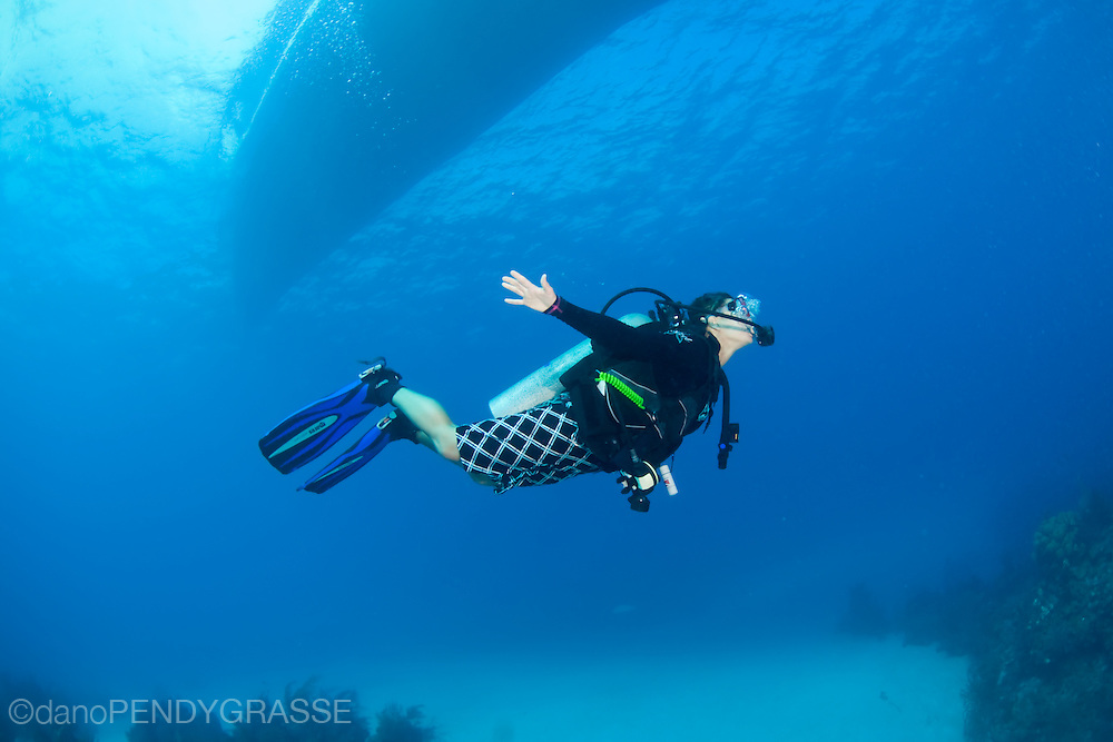 "A girl ""flies"" underwater beneath a ""liveaboard"" dive boat in Belize, Central America."