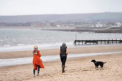 Portobello, Scotland, UK. 28 March, 2020. On the first weekend of the coronavirus lockdown the public were outdoors exercising and maintaining social distancing along Portobello beachfront promenade. Two females walking dog on beach.  Iain Masterton/Alamy Live News