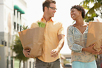 Couple walking with groceries portrait