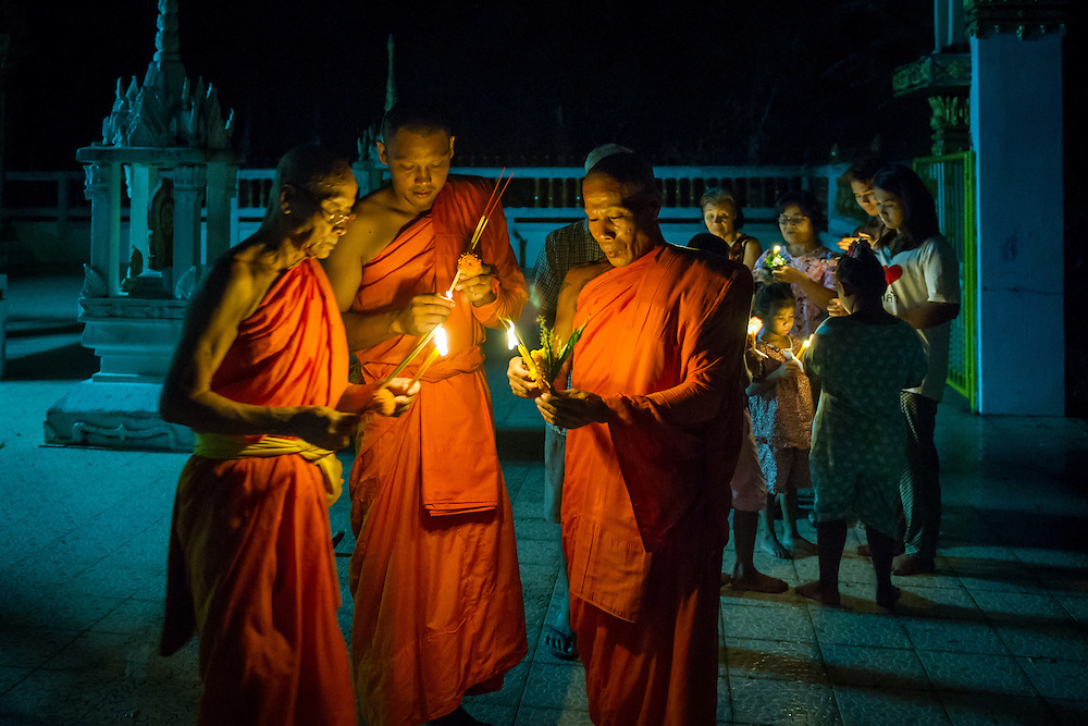 Monks light candles to celebrate Visakha Puja Day in rural Thailand. PHOTO BY LEE CRAKER