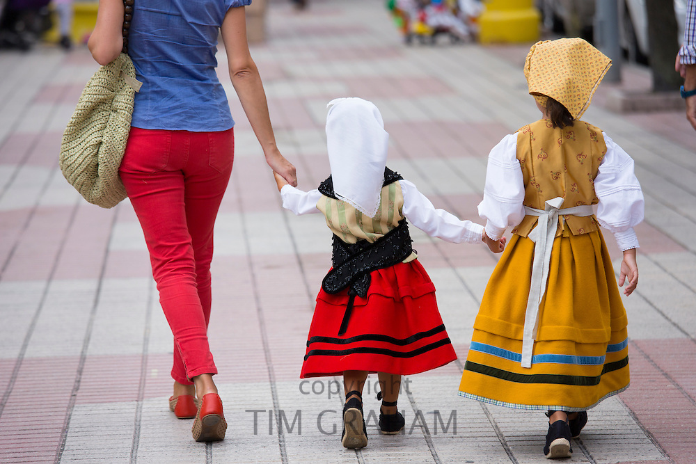 Little girls in attractive traditional costume walking to fiesta at Villaviciosa in Asturias, Northern Spain
