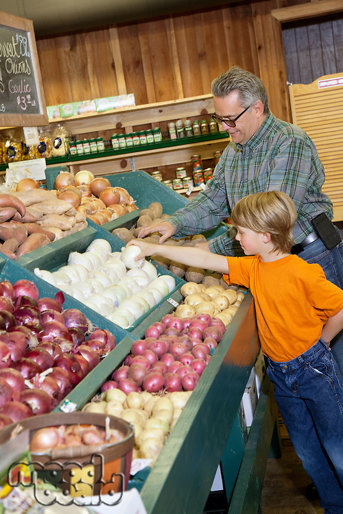 Young boy with grandfather selecting white onions at vegetable stand in produce market