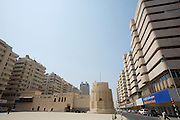 Al-Hisn Fort surrounded by modern buildings.