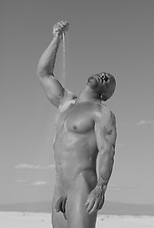 nude muscular man pouring sand on his body