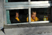 China, Taiyuan, 2008. On a cold day in February, this mother and child enjoy the heat inside and a view of the street..