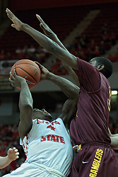11 January 2014:  Bobby Hunter attempts to twist his way past the defending arms of Christian Thomas during an NCAA  mens basketball game between the Ramblers of Loyola University and the Illinois State Redbirds  in Redbird Arena, Normal IL.  Redbirds win 59-50