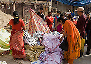 Colorfully dressed women shop for bright fabrics in Durbar Square, Kathmandu, Nepal.