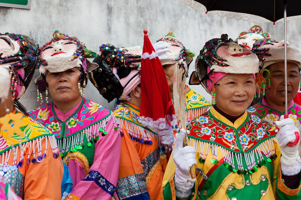 Middle aged and elderly ladies in costume ahead of the ceremony to honor the Bao Sheng Emperor in Taipei's Bao An Temple