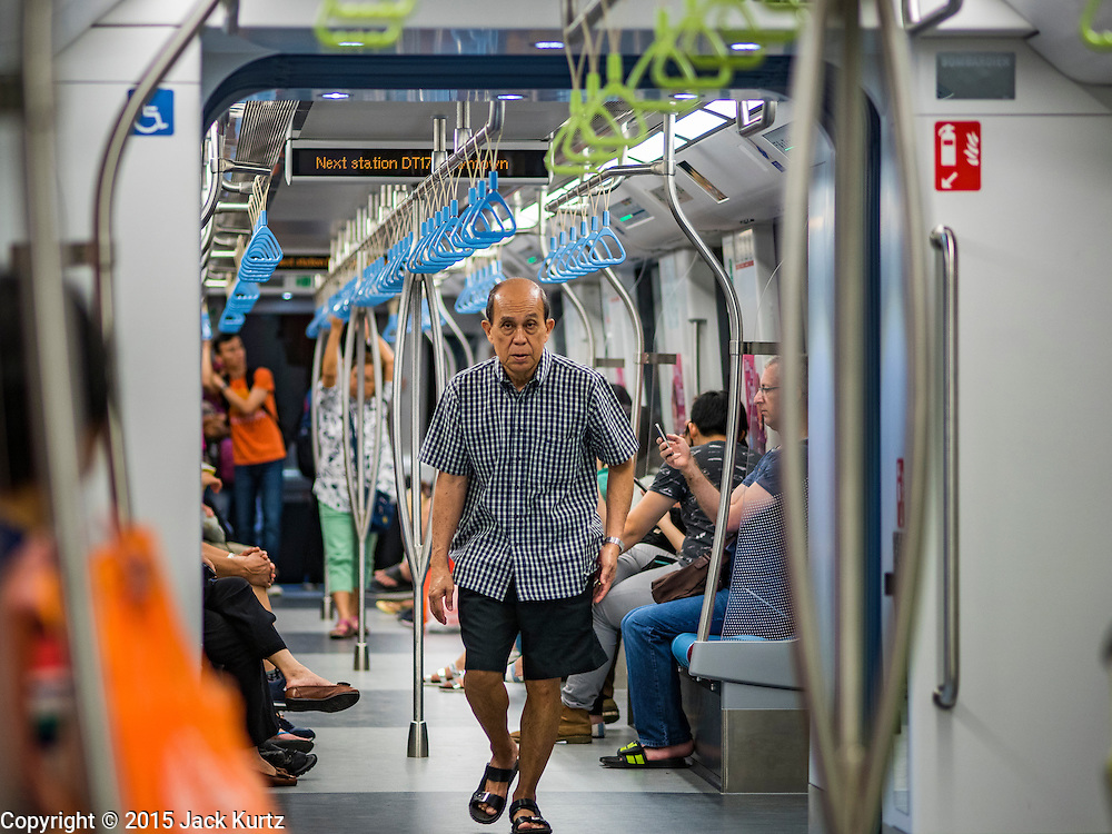 """27 DECEMBER 2015 - SINGAPORE, SINGAPORE:  A man walks through the train on the expanded Downtown Line on the first day of service on the new line. Singapore opened the extension of the Downtown Line on its subway system Sunday. The extension is a part of Singapore's plans to make the city-state a """"car lite"""" metropolis with plans to double the current subway to more than 360 kilometers of track by 2030. The government plans to have 80% of homes within a 10 minute walk of a subway station.   PHOTO BY JACK KURTZ"""
