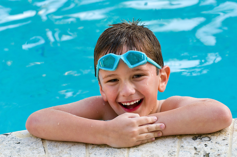 5 year old kid laughing in a swimming pool.