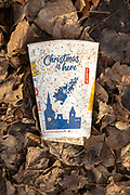Discarded McDonald's take-away drink carton cup on floor on top of leaf litter,  'Christmas is here' message, UK