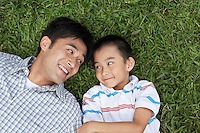 Father and son (7-9) lying on grass looking in eyes elevated view