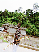 Young Jawara man wearing western clothing with bow and arrow on the ferry landing, Middle Andaman Island