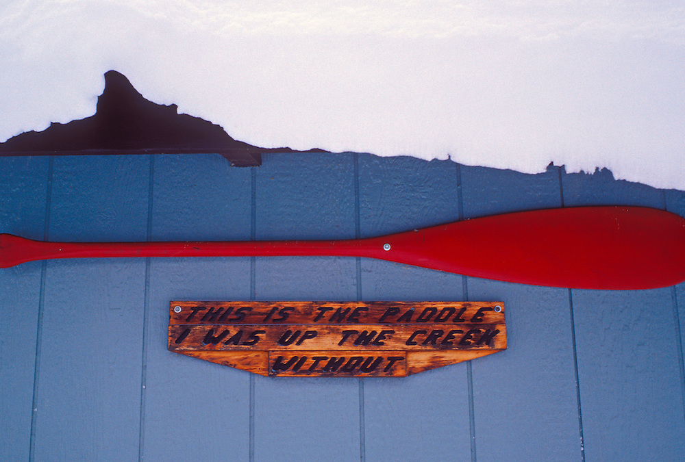A red canoe paddle hangs under the snow-covered eves of a garage in Silver City, Mich. with a humorous sign.