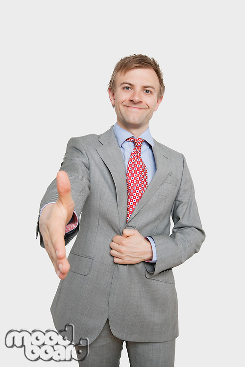 Portrait of handsome young businessman extending hand for a handshake