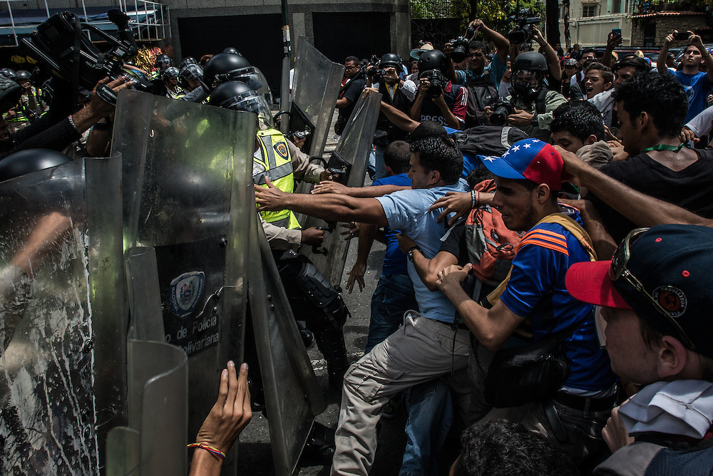 CARACAS, VENEZUELA - JUNE 9, 2016: Hundreds of university students marched in downtown Caracas in protest against the government and its policies that have caused massive shortages of food across the country, among other problems. The students want President Nicholas Maduro to step down from power.  Soon after they started marching, hundreds of National police officers created blockades to prevent the students from passing.  The confrontation turned violent, with students throwing rocks and molotov cocktails at the police, who responded with rubber bullets, tear gas, and unleashing a water cannon on them. Venezuela is convulsing from a raft of violence triggered by hunger. It is the latest chapter of an economic collapse which has left the country neither able to produce its food nor import it from abroad, leaving a nation searching for how to feed itself. PHOTO: Meridith Kohut