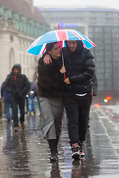 © Licensed to London News Pictures. 03/01/2016. London, UK. A couple with an umbrella walk across Westminster Bridge in London.   London and the UK has experienced heavy rain and wind today. Photo credit : Vickie Flores/LNP